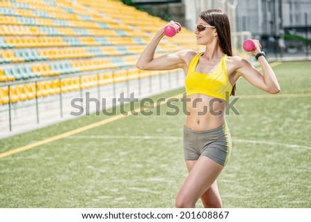Slim figure and a healthy body. Fitness woman in tracksuit and dumbbell training on the football field on a hot sunny day. - stock photo