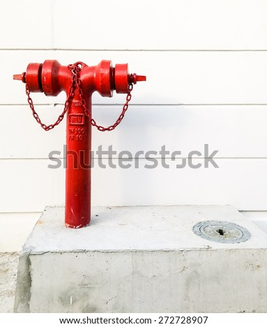 Slim fire hydrant near the wall of urban village. - stock photo