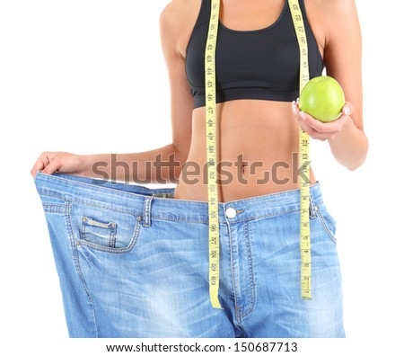 Slim girl in big jeans isolated on white - stock photo