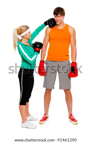 Slim girl in boxing gloves punching man isolated on white - stock photo