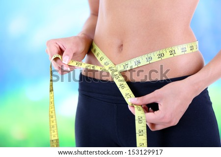 Slim girl with centimeter isolated on white - stock photo