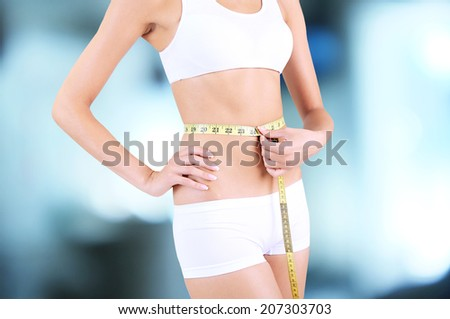 Slim girl with tape on bright background - stock photo