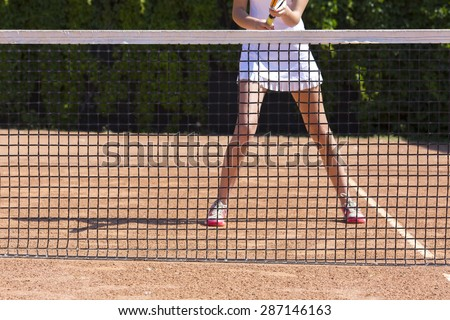 Slim legs of female tennis athlete behind fishnet barrier. Young woman stays in ready position close to tennis playground barrier ready to return the ball white dress miniskirt focus on legs - stock photo