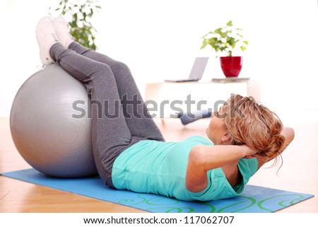 slim mid aged woman do her exercises with abs ball at home - stock photo