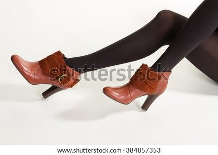 Slim model wears brown shoes. Brown ankle boots with insets. Black tights and brown footwear. Dark pantyhose with brown shoes. - stock photo
