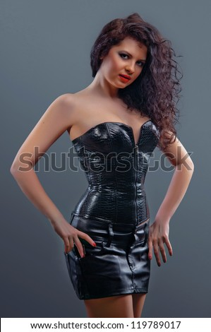 Slim sexy woman with hourglass figure in black leather corset - stock photo