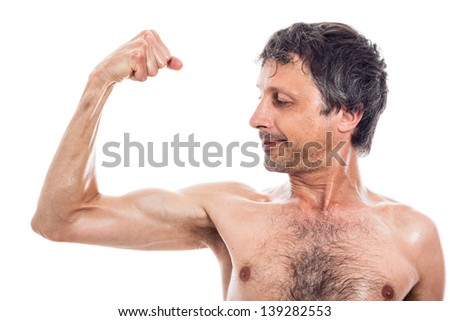 Slim shirtless man looking at his biceps, isolated on white background - stock photo