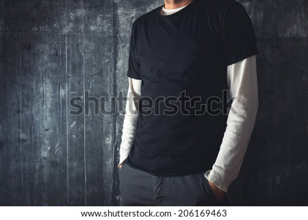 Slim tall man posing in blank black t-shirt as copy space for your text or design. - stock photo