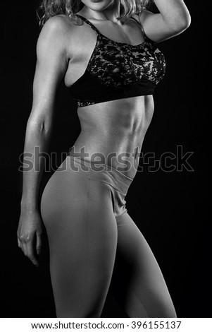 Slim tanned woman's body over dark grey background - stock photo