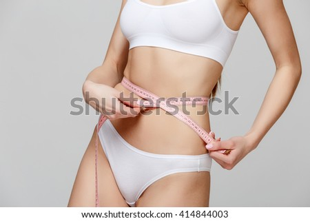 Slim tanned woman's body over gray background - stock photo