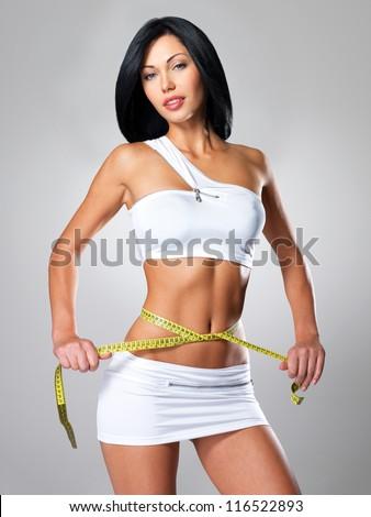 Slim woman and measure tape around her body - a studio shot - stock photo