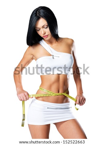 Slim woman and measure tape around her body - a studio shot - stock photo