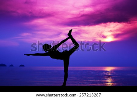 Slim Woman making yoga on the beach in the sunset - stock photo