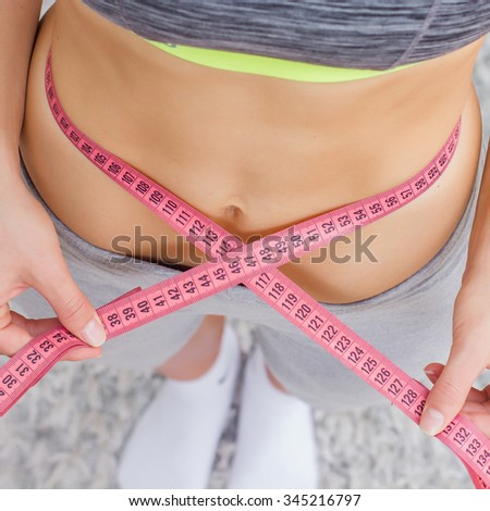 Slim Woman Measuring her thin waist with a tape measure. Caucasian fitness young female.Unrecognizable person.Diet and weight loss concept. - stock photo