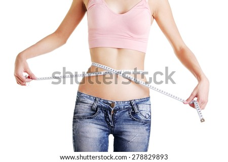 Slim woman measuring her waistline - stock photo