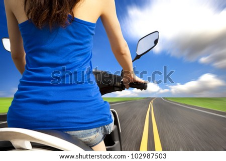 slim woman riding scooter with high speed on the road - stock photo