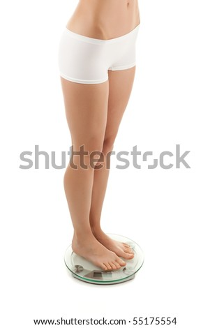 Slim woman standing on weight isolated on white background - stock photo