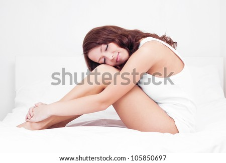 slim young brunette woman sleeping on the white linen in bed at home - stock photo