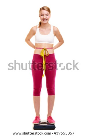 Slimming and weight loss. Happy joyful young woman girl measuring with tape measure on weighing scale. Healthy lifestyle concept. Isolated on white. - stock photo