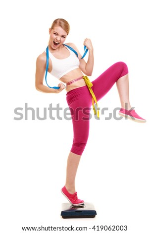 Slimming and weight loss success. Happy young woman girl measuring with tape measures on weighing scale clenching fists. Healthy lifestyle concept. Isolated on white. - stock photo
