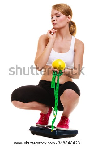 Slimming diet weight loss. Upset unhappy sad young woman girl with measuring tape on weighing scale holding grapefruit. Healthy lifestyle concept. Isolated on white background. - stock photo