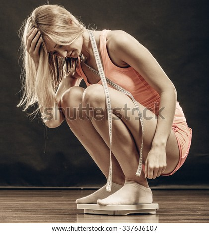 Slimming diet weight loss. Upset unhappy young woman girl with measure tape on weight scale. Healthy lifestyle concept. - stock photo