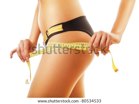 slimming woman measuring her body on white background - stock photo