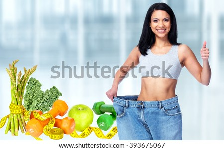 Slimming woman wearing big pants over blue background. - stock photo