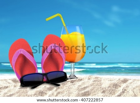 Slipper with sungalsses and orange drinks on a beach - stock photo