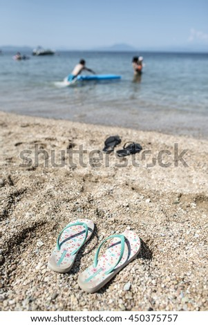 Slippers in the sand on the beach and people at sea.  - stock photo