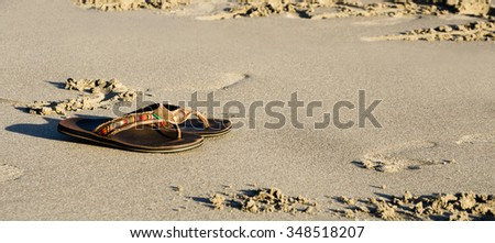 Slippers on a sand beach at sunset - stock photo