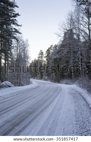 Slippery and snow road curving left on a cold winter morning. Image taken during sunrise after the first snow covered up the ground. It's mandatory to wear winter tires in Finland in winter time. - stock photo