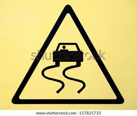 Slippery when wet road sign - stock photo