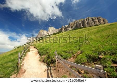 sloping mountain trail in the Italian Dolomites - stock photo