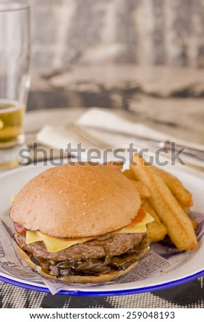 Sloppy Joe beef burger with cheese and onions served with extra chunky thick chips. Glass of beer in the background to the left and cutlery to the right. - stock photo