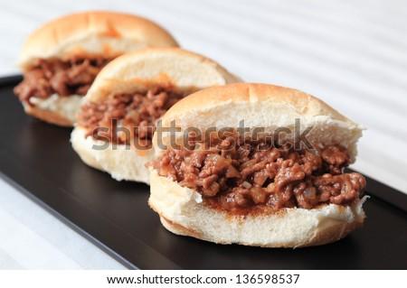 Sloppy Joe Sliders - Three home-made Sloppy Joe slider sandwiches on a black serving tray. - stock photo