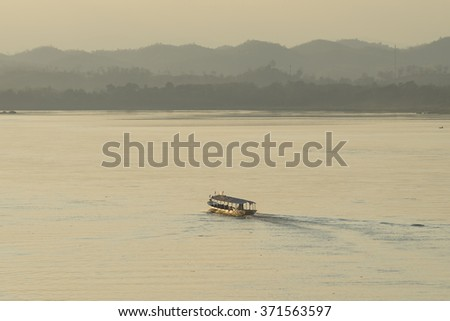 Slow boat cruise on the Mekong River in Laos at evening. - stock photo