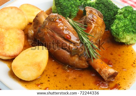 Slow-cooked lamb shank with roast potatoes and broccoli. - stock photo