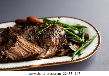 Slow cooked pot roast with carrots, green beans, onions, garlic and gravy on a white porcelain platter with gold rim against a gray tablecloth.  - stock photo