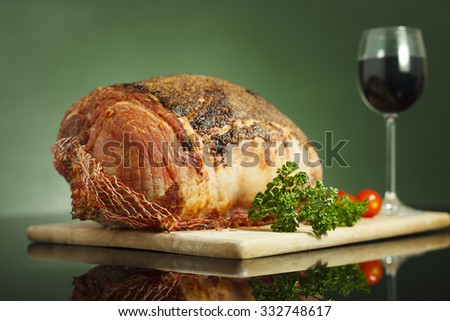 Slow cooked roast beef  covered with mustard sauce, baby tomatoes and red wine glass on reflective surface and green background - stock photo