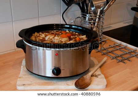 Slow cooker cooking Scouse in a Kitchen with some kitchen items in view - stock photo
