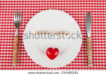 Slow-food lettering on a white plate - slow-food concept - stock photo