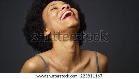 Slow pan up casual black woman laughing and smiling - stock photo
