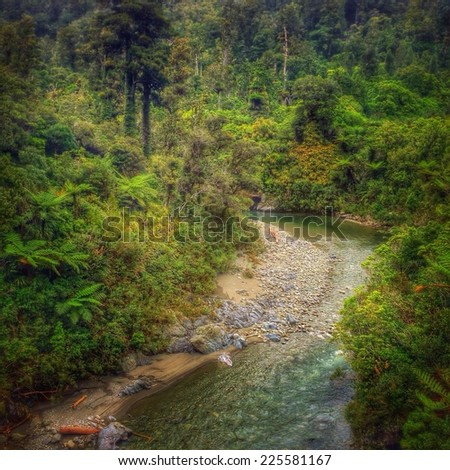 Slow running stream through a wooded valley bottom. - stock photo