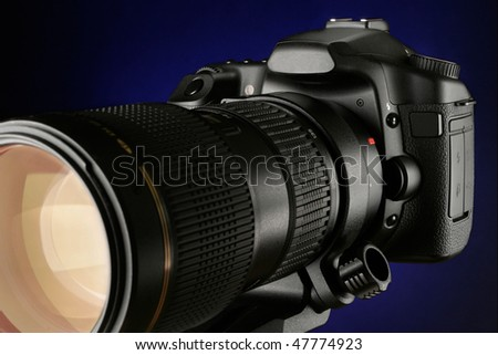 SLR digital camera with Tele photo zoom lens on a blue gradient background - stock photo