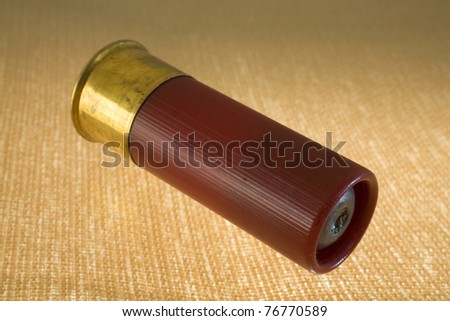 slug in a 12 gauge shotshell on a bright yellow and brown background - stock photo