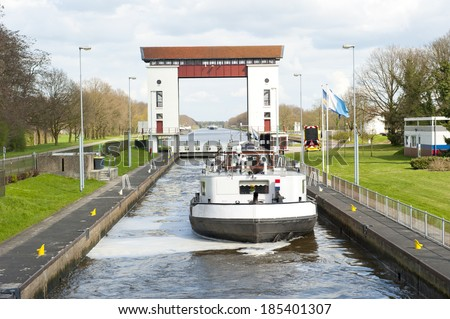 Sluice complex with water filled reservoir and passing cargo ship - stock photo