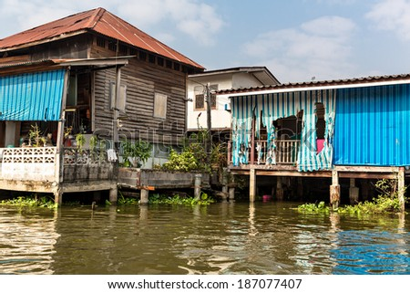 Slum on dirty canal in Asia - stock photo