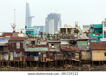 Slum wooden house on the Saigon river bank, in front of modern buildings, in Ho Chi Minh city, Vietnam - stock photo