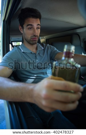 Slumped man with alcohol bottle while driving car - stock photo